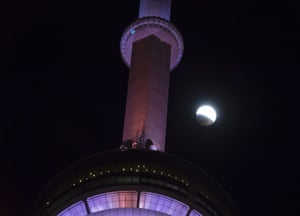 An eclipse of the moon progresses behind the CN Tower in Toronto. The entire eclipse will exceed three hours