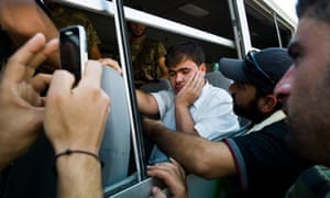 A man sits on a bus having been detained by rebels in Aleppo