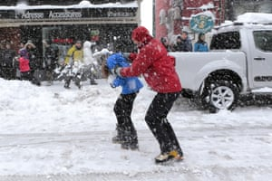 Students play in the snow along a street in Corte