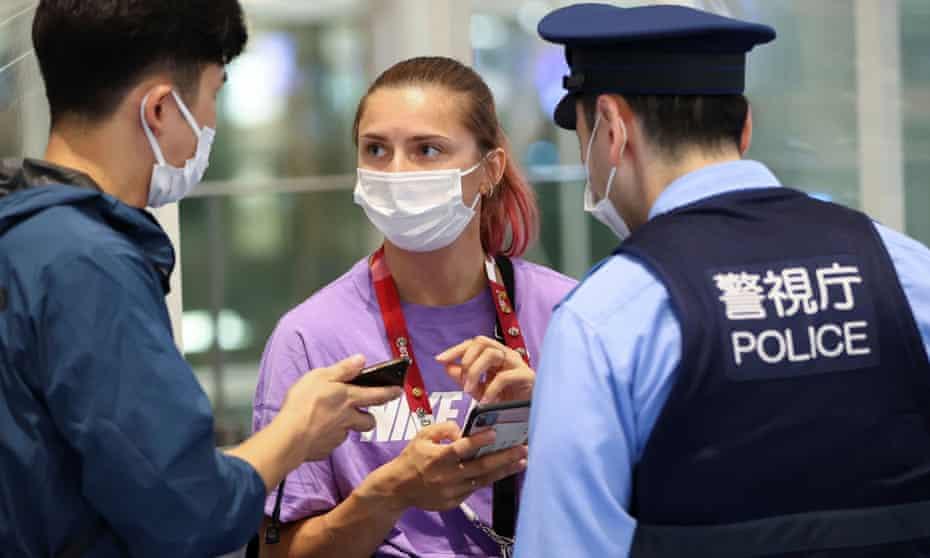 Belarusian athlete Krystsina Tsimanouskaya with police at Haneda airport in Tokyo on Sunday night
