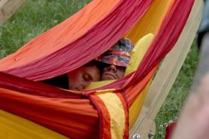Festival goers sleep in a hammock