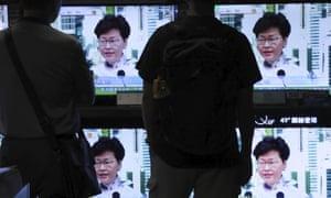 Hong Kong residents watch TVs broadcasting Carrie Lam's speech.