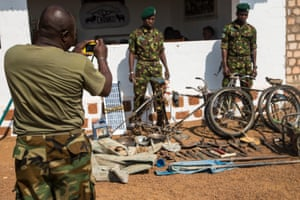 Two rangers pose for a photo next to machetes, knives, spades and other equipment which have been confiscated from poachers and laid out at Chinko's HQ.