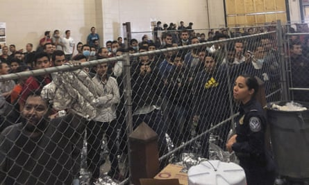 Men stand in a US border detention center in McAllen, Texas, 12 July 2019, as Mike Pence visited.