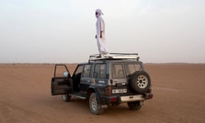 Toubou human smuggler Barka al Qatrun looks out for cars driven by his colleagues coming from Libya at a checkpoint outside Agadez.
