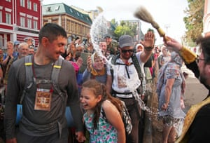 Russian Orthodox priest sprinkles pilgrims with holy water