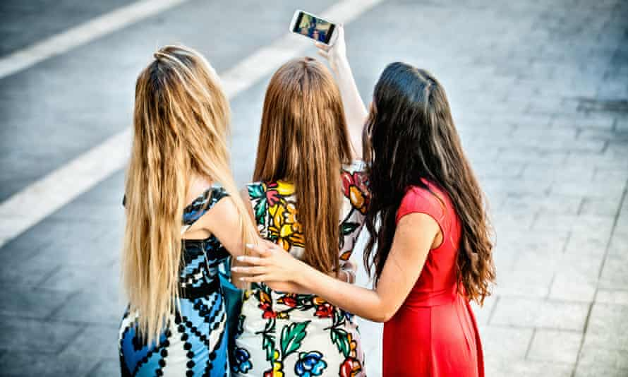 Rear view of three young women taking selfie with smartphone