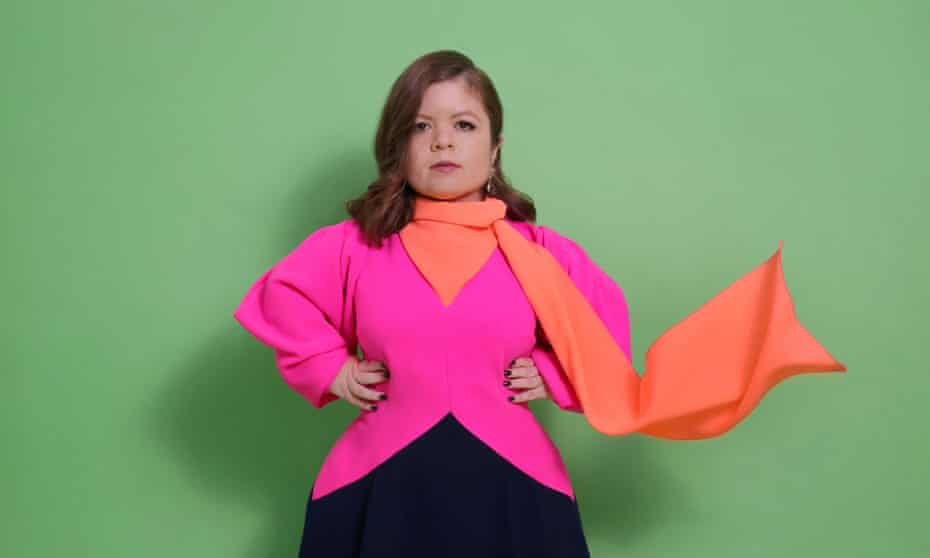 Portrait of Sinéad Burke wearing pink top with hands on hips
