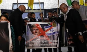 Palestinian protesters hold up a picture of Donald Trump