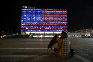 A woman plays with her dog outside the municipality building in Tel Aviv, lit in the colors of the American flag
