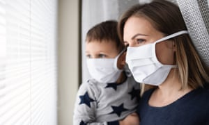Mother and small son with face mask indoors at home