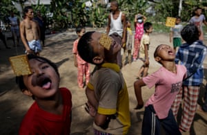 Yangon, Myanmar – Boys attempt to eat hanging biscuits during independence day celebrations.