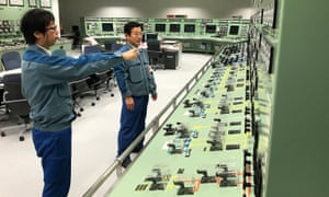 Tokyo Electric Power employees check instruments in a mock-up of the plant's central control room.