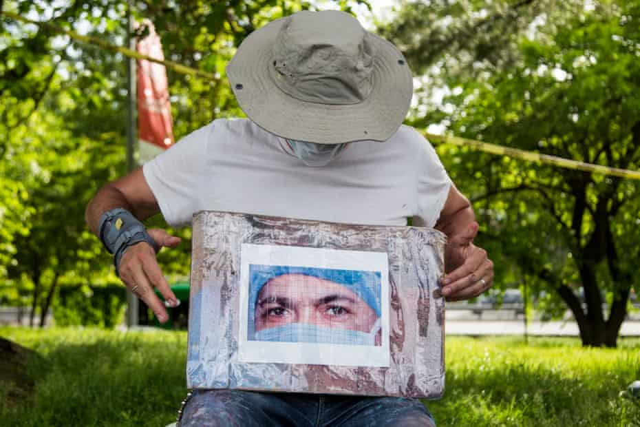 Artist Jorge Rodríguez holds up a photo of Dr. Ydelfonso Decoo while painting a mural in Queens, New York. Dr. Ydelfonso Decoo, an immigrant doctor, died of complications from Coronavirus.