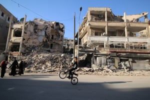 A boy rides a bicycle past damaged buildings in the rebel-held Seif al-Dawla neighbourhood