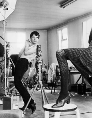 David Bailey, in a vest and tight trousers, hands clasped, bending a little backwards, with Jean Shrimpton's leg resting on a table