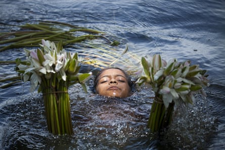 A girl collects water lilies from a lake in Bangladesh