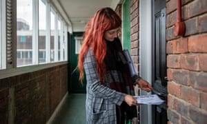Volunteer Jessica Kleczka posts a leaflet for a local community support group called Mutual Aid through a letter box on a housing estate near the Caledonian Road in north London.