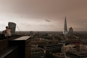Office workers stand on their balcony to photograph the darkened sky/