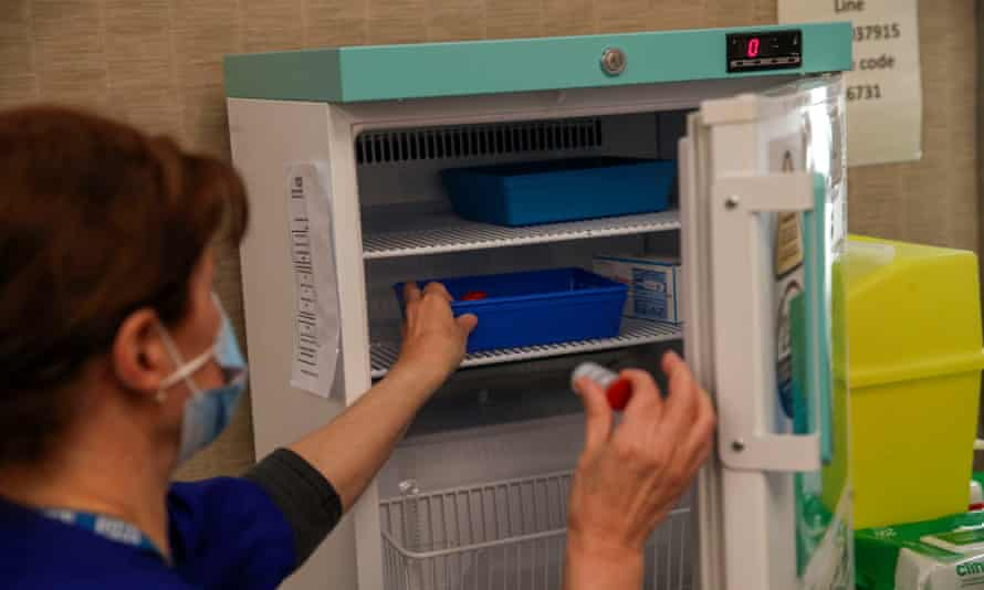 Gwendelina Duquette takes a vial of the Moderna Covid-19 vaccine from the fridge at the vaccination centre at the Madejski Stadium in Reading, Berkshire