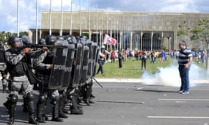 A protester stands in front of a line of riot police in Brasilia on Wednesday.