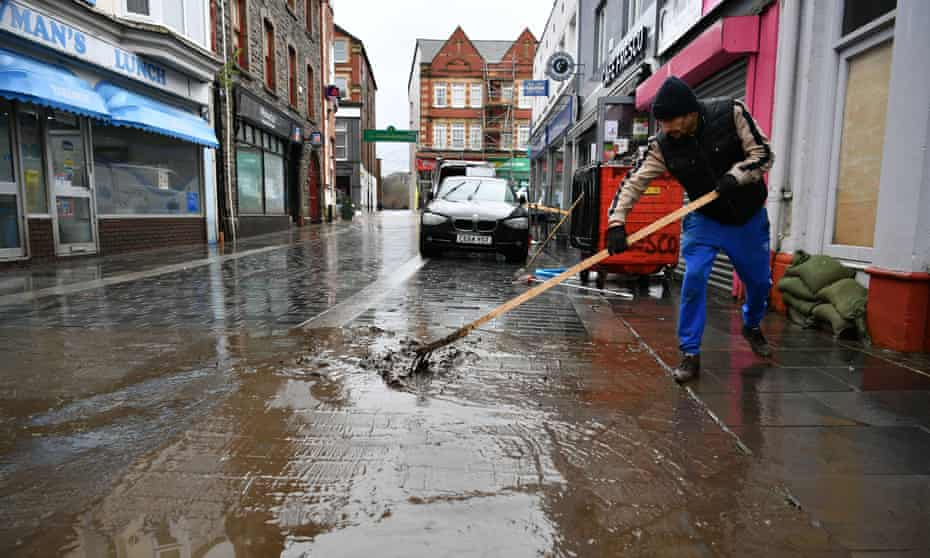 A man cleans up the street in Pontypridd after Storm Dennis caused flooding in February 2020