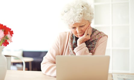 Senior woman at home reading something on her laptop
