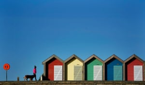 Blyth, UK. Blue skies on a cold morning as a woman walks her dog past beach huts, in Northumberland