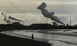 view of Port Talbot smokestacks over lonely beach