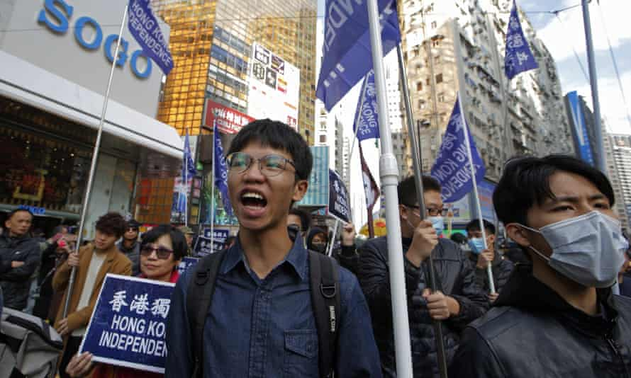 Tony Chung, left, marches during a pro-democracy protest in Hong Kong.