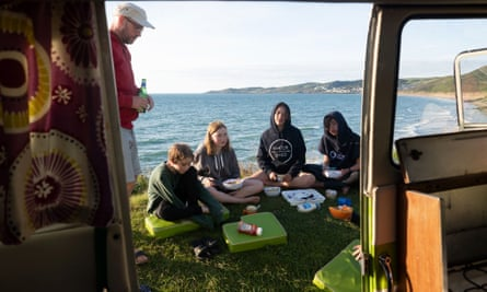 Family picnicking by van with sea in background