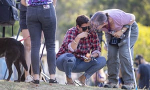 A Canungra fire evacuee is comforted outside Moriarty Park Hall where they attended a community meeting about the fires in the region