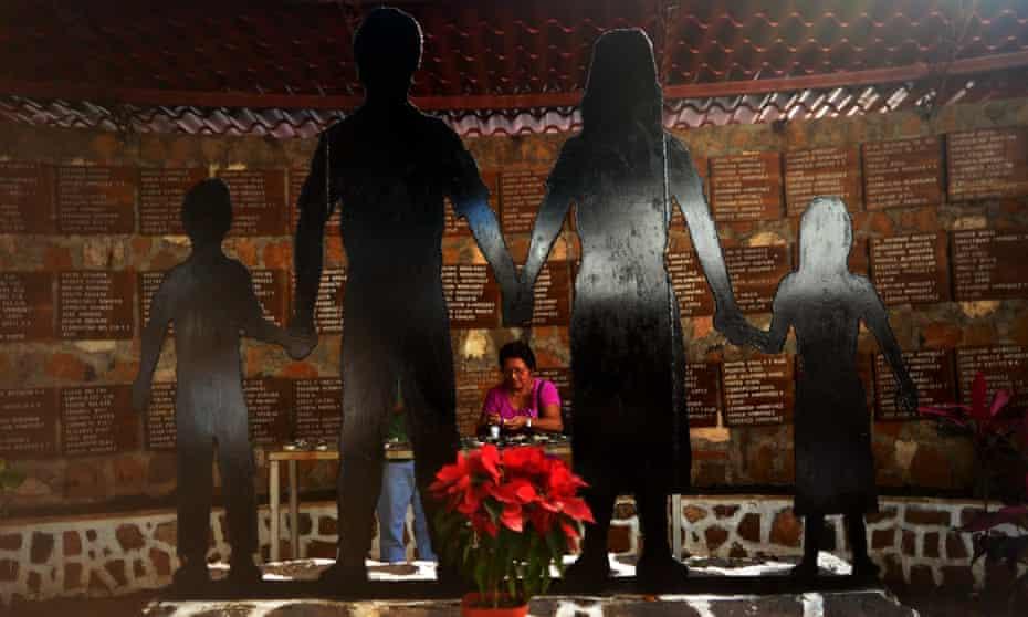 A woman lights a candle at the memorial for the massacre victims in the village of El Mozote, El Salvador