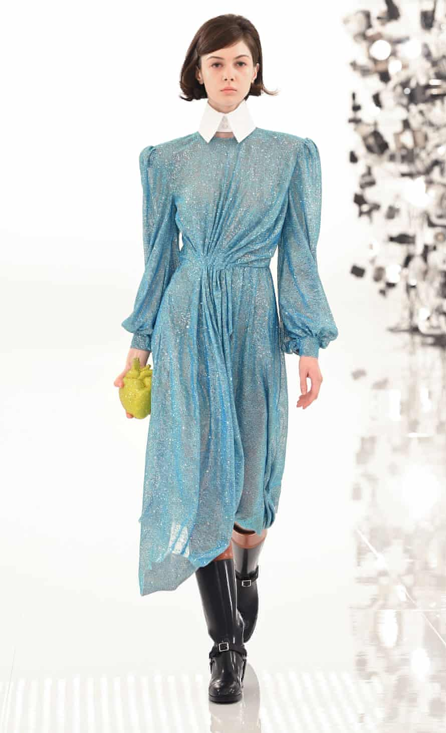 model wears long blue dress with black riding boots