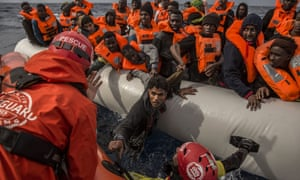 Aid workers rescue migrants aboard an overcrowded rubber boat 60 miles north of the Libyan coast.