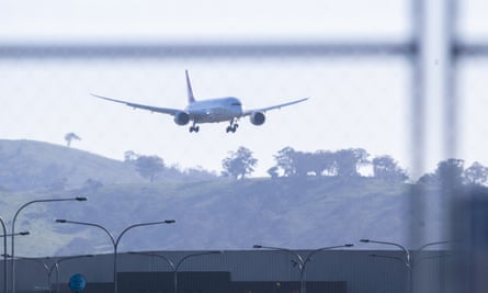 A plane flies over an airport