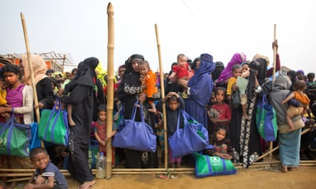 Rohingya Muslim women with their children stand in a queue outside a food distribution center at Balukhali refugee camp, Bangladesh.