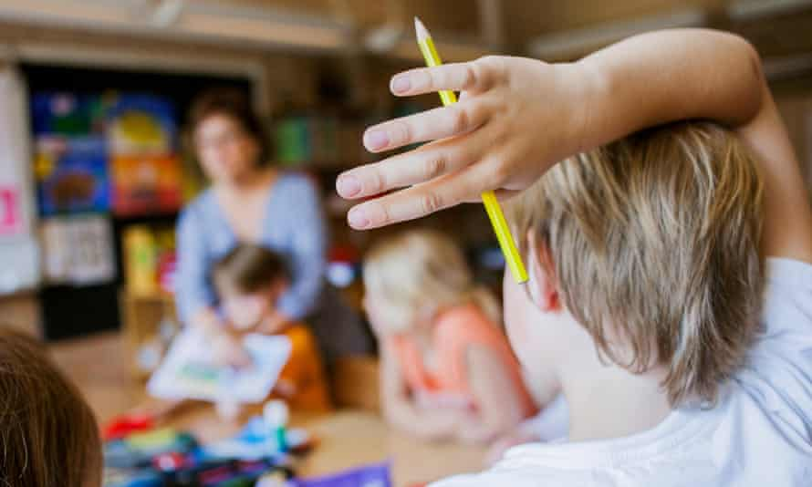 Boy raises his hand in a classroom