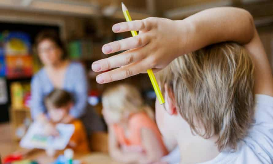 Boy with pencil raising hand in classroom
