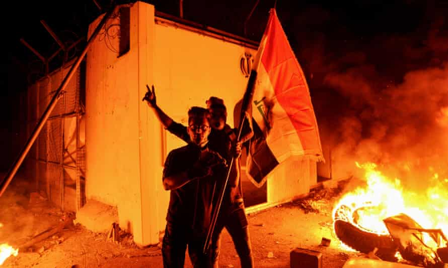 Iraqi demonstrators gesture as flames start consuming Iran's consulate in Najaf on Wednesday.