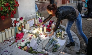 A woman lights a candle at a makeshift memorial in Saint-Etienne-du-Rouvray, France, on 26 July.