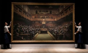 Sotheby's staff hold Banksy's Devolved Parliament.