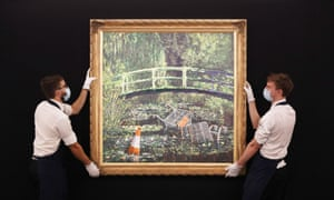Technicians handling Banksy's Show Me the Monet at Sotheby's in central London.