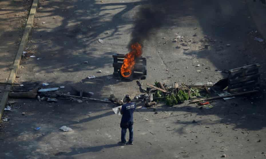 A demonstrator stands near a fire during clashes with security forces in Caracas on 1 May.