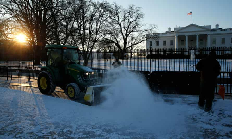 Snowploughs work to clear the pavement in front of the White House ahead of Friday's expected storm.
