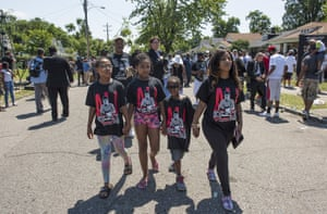 Ashlee Brown, of Louisville, walks down the street with her kids, all wearing the same Ali t shirts, after the funeral procession motorcade passed by