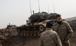 Turkish soldiers prepare their tanks before crossing the Syrian-Turkish border at Hatay.