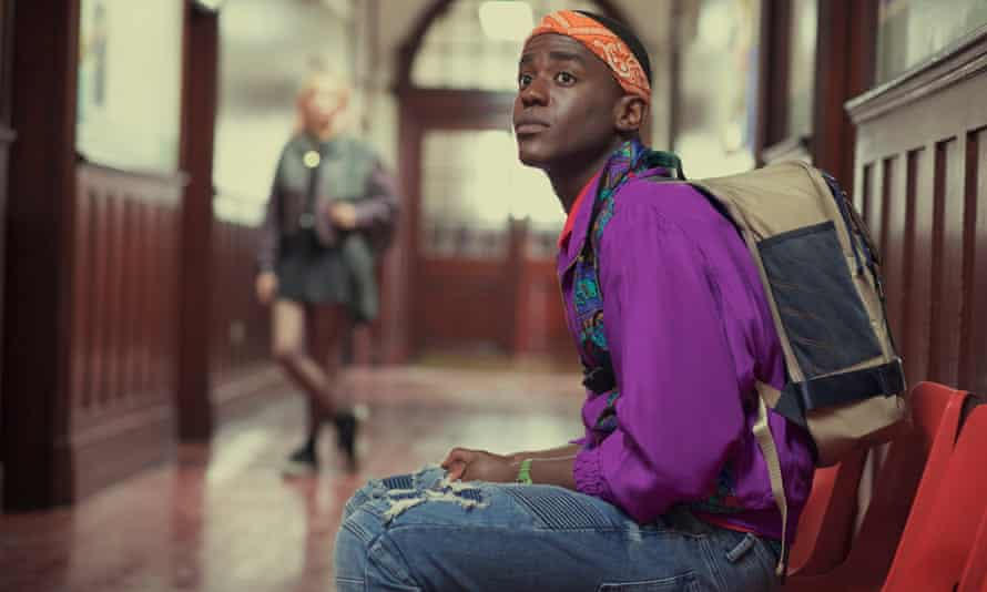 Ncuti Gatwa as Eric Effiong, wearing a purple top and denim dungarees and sitting in a chair in a school corridor, staring and looking slightly anxious, in a scene from Sex Education.