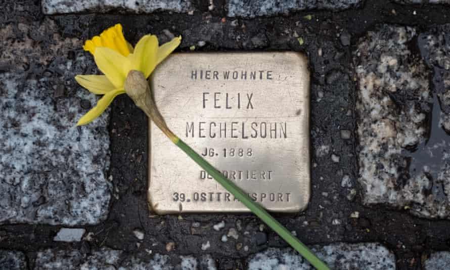 Una flor posada sobre un Stolperstein individual a Berlín.