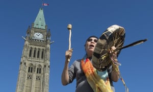 Marcia Brown Martel, who was taken from her home as a child and adopted by non-indigenous parents, sings outside the parliament buildings in Ottawa.